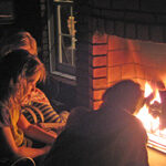 Children read by outdoor fireplace
