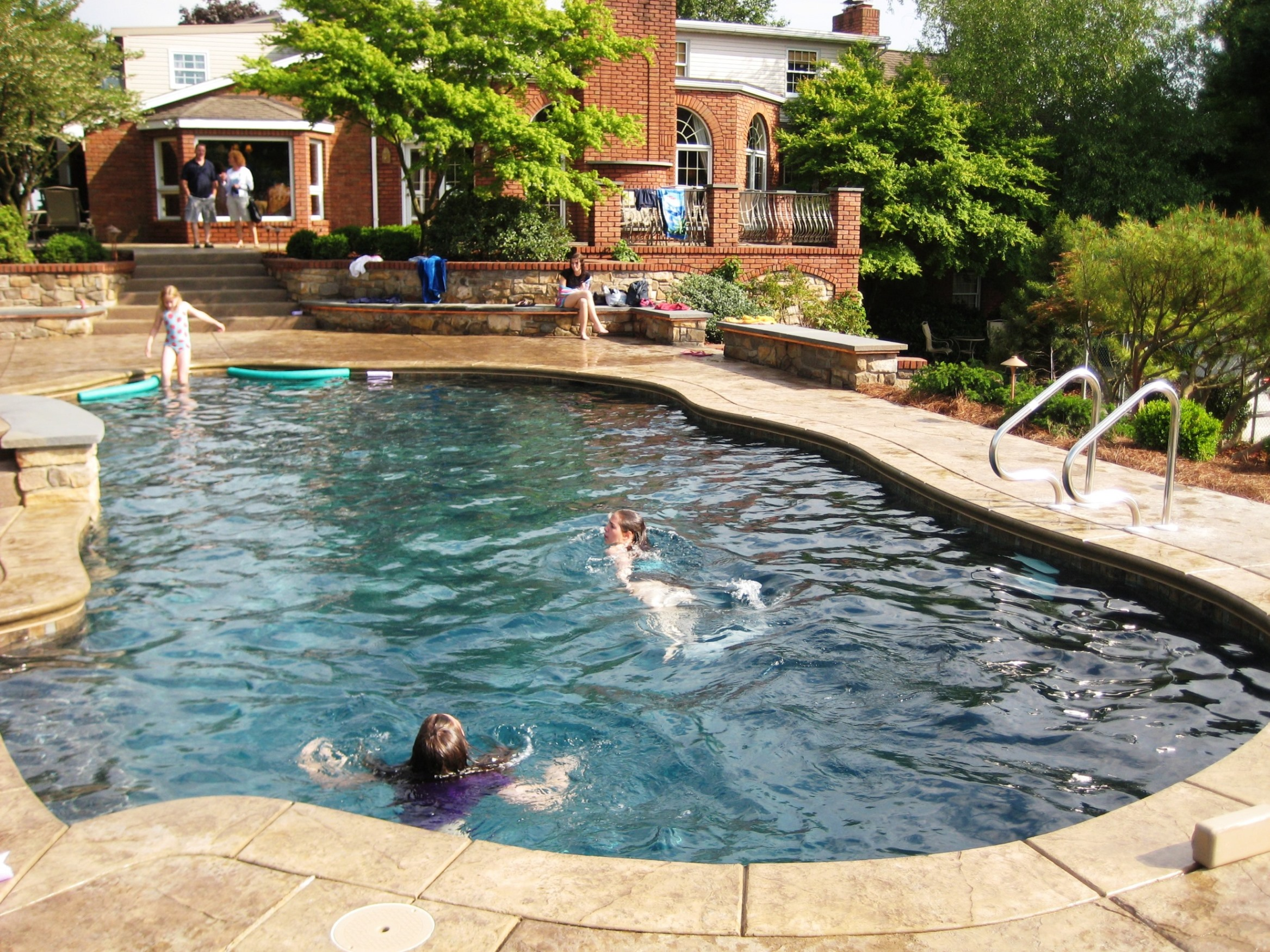 Custom pool-side terraces add seating (without clutter) for gatherings around pool with built-in swim jets, Lancaster, PA