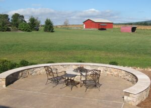 Rural farm vista surrounds this stone fire pit with gas fire and seating wall, Manheim, PA