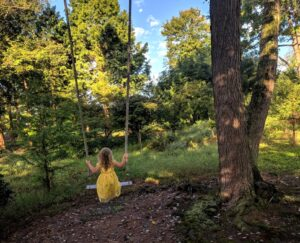 Granddaughter swings in a woodland garden, Manheim, PA