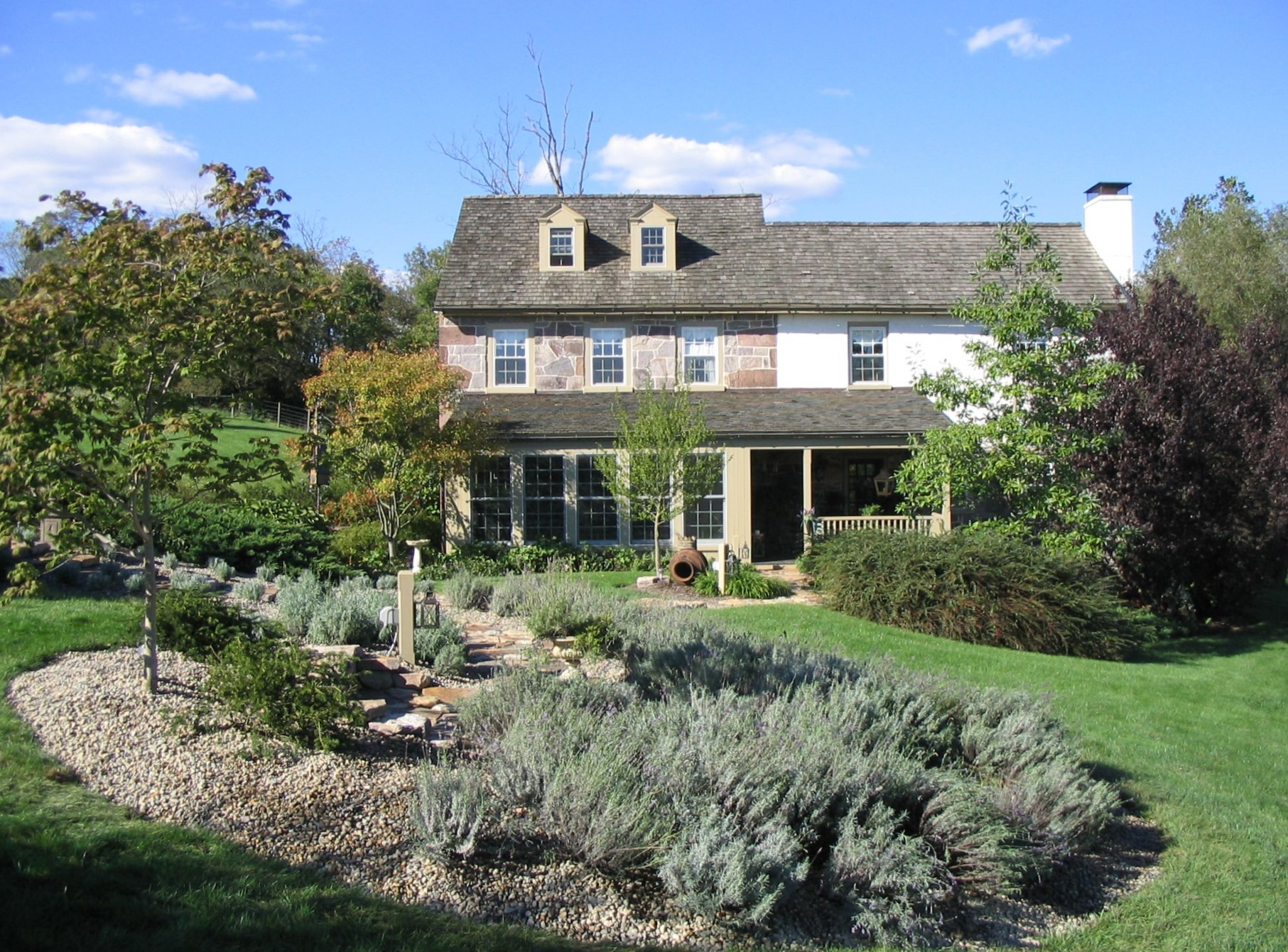 Mediterranean-inspired herb garden and rustic stone paths complement farmhouse landscape, Morgantown, PA