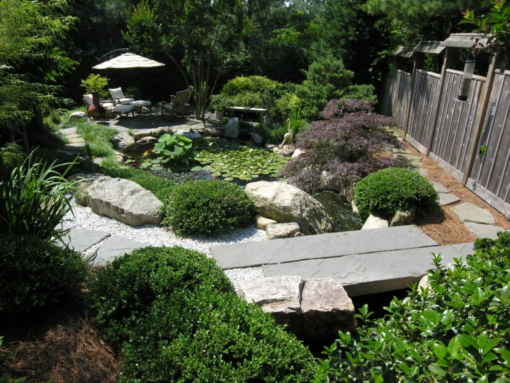 Custom stone bridge crosses stream above Koi pond with Lotus and Waterlilies, Wyomissing, PA