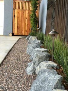 Rugged boulders form retaining wall and gravel curb, San Diego, CA