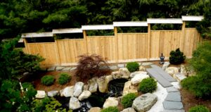 Custom privacy fence with Japanese-style roof steps down hillside garden, Wyomissing, PA