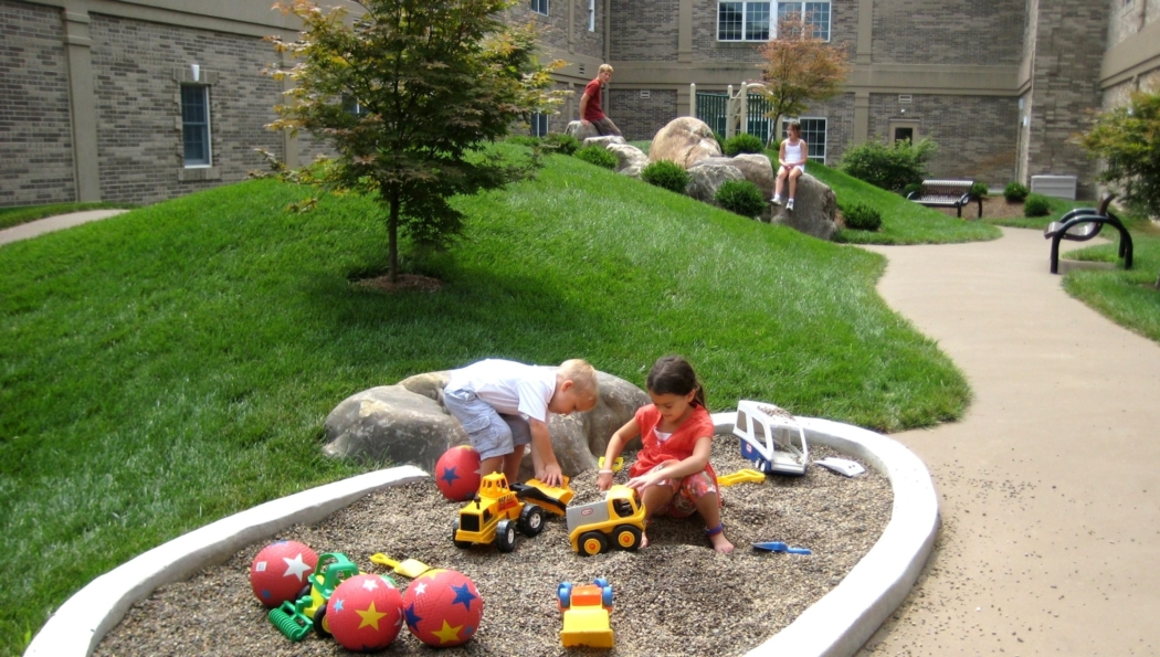 Children enjoy a simple playground of grassy hills surrounded by a tricycle path, in the safety of an enclosed pre-school courtyard, Lancaster, PA